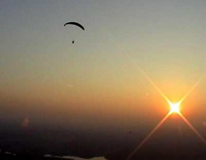 The buggy being flown past a sunset.